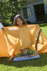 Brother and sister (8-10) assembling tent on garden lawn, girl sitting on top of boy, holding orange outer tent canvas, smiling, portrait (tilt)
