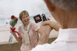 Senior woman standing beside fountain, holding bouquet of red roses, smiling, man filming her with portable video recorder (tilt, differential focus)
