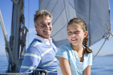 Father and daughter (8-10) sitting on deck of sailing boat, smiling, portrait