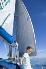 Father and daughter (8-10) on deck of sailing boat, man standing beside sails, focus on girl in foreground, smiling, portrait