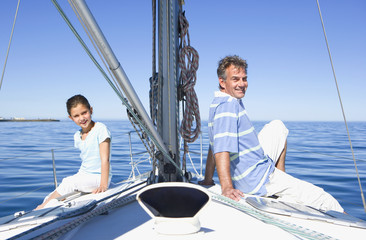 Father and daughter (8-10) sitting back to back at bow of sailing boat, smiling, side view, portrait