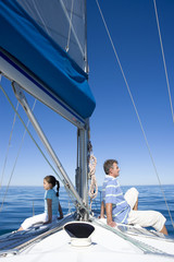 Father and daughter (8-10) sitting back to back at bow of sailing boat, smiling, profile