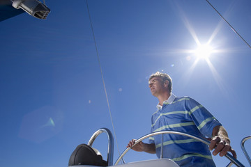 Man in striped blue polo shirt standing at helm of sailing boat out at sea, steering, low angle view (lens flare)