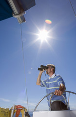 Man in striped blue polo shirt standing at helm of sailing boat out at sea, looking through binoculars, low angle view (lens flare)