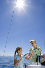 Mother and daughter (8-10) standing at helm of sailing boat out at sea, steering, smiling (lens flare, tilt)