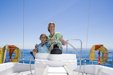 Mother and daughter (8-10) standing at helm of sailing boat out at sea, steering, smiling, front view, portrait