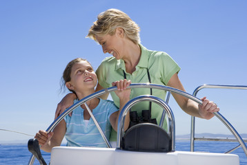 Mother and daughter (8-10) standing at helm of sailing boat out at sea, steering, smiling at one another, front view
