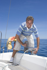 Man standing on deck of sailing boat out to sea, winding rope pulley of boat rigging, smiling, front view, portrait