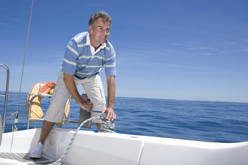 Man standing on deck of sailing boat out to sea, winding rope pulley of boat rigging, smiling (tilt)