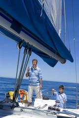 Father and son (8-10) standing at helm of sailing boat out to sea, boy steering, man holding rigging, smiling
