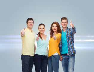 group of smiling teenagers showing thumbs up