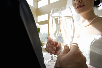 Bride and groom making celebratory toast with champagne flutes, close-up, mid-section