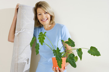 Senior woman holding pot plant and rolled up carpet, moving house, smiling, front view, portrait