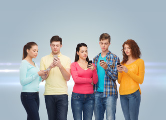 group of serious teenagers with smartphones