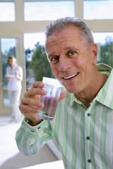 Senior man drinking glass of water at home, mature woman in background, focus on man, smiling, side view, portrait