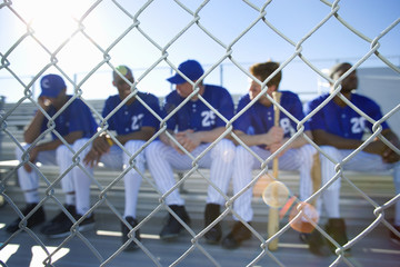 Baseball team sitting on bench in stand during competitive baseball game, view through wire fence, front view (lens flare)