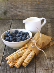 sesame sticks, blueberries and milk on wooden background