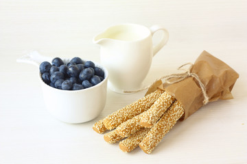 sesame sticks, blueberries and milk on white background horizon