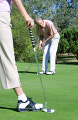Mature couple standing on putting green, man playing shot, woman watching in foreground
