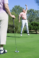 Mature couple playing golf, man punching air in delight at successful putt, woman watching in foreground