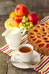 strawberry cake with tea, milk and fruit for breakfast