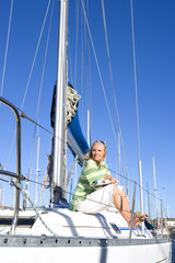 Mature woman, in green striped jumper, sitting on deck of yacht moored at harbour jetty, looking away, thinking