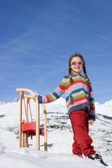 Girl (7-9) standing in snow by sled, wearing sunglasses, smiling, portrait, mountain range in background