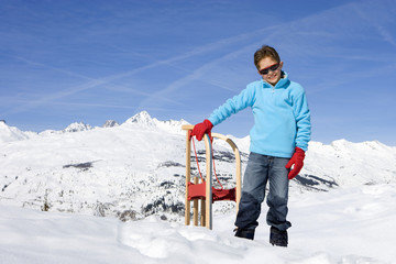 Boy (7-9) standing in snow by sled, wearing sunglasses, smiling, portrait, mountain range in background