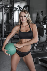 Blonde woman with medicine ball in gym