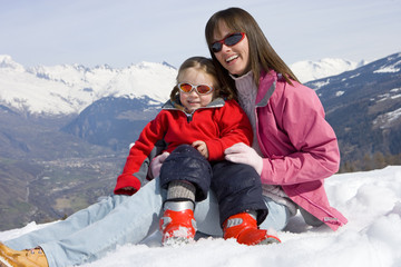 Mother and daughter (6-8) sitting together in snow field, wearing sunglasses, smiling, portrait, mountain range in background