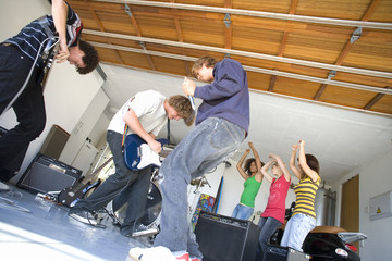 Group of teenagers (16-18) playing in garage band, low angle view
