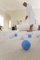 Senior couple in bedroom, man practising golf putt, focus on golf balls in foreground