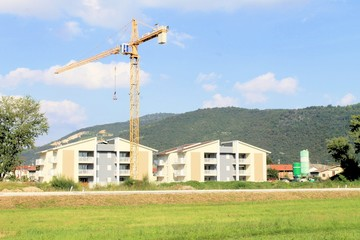 view of houses under construction with crane