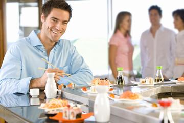 Young man sitting at sushi bar, smiling, portrait