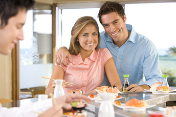 Young couple sitting at sushi bar, smiling, portrait