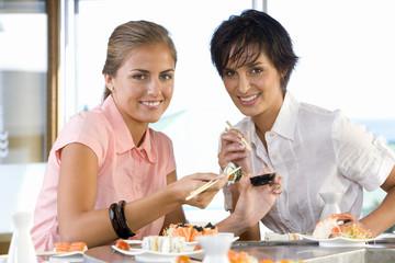 Two women eating in sushi bar, smiling, portrait