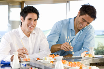 Two men eating in sushi bar, smiling, portrait