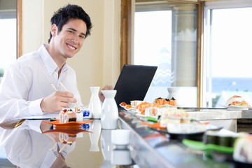 Young man eating in sushi bar, smiling, portrait