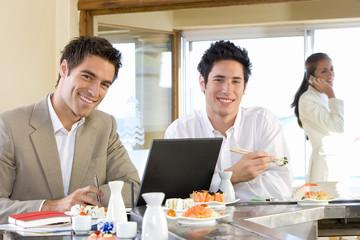 Two men eating in sushi bar, smiling, portrait