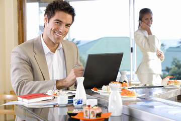 Man with laptop in sushi bar, smiling, portrait