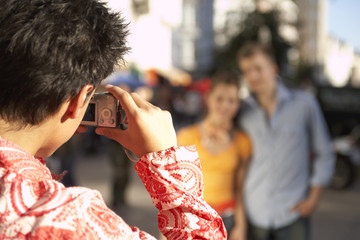 A boy taking a photo with his digital camera.