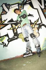 A teenage boy wearing rollerblades.
