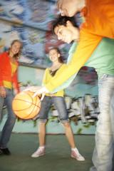Teenagers playing basketball.