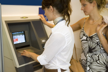 Women at an ATM machine.