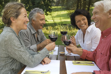 Two mature couples drinking wine