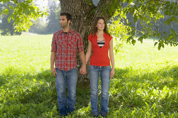 A couple leaning against a tree.