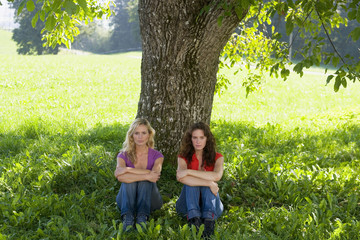 Two women sitting apart, leaning against a tree.
