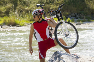 A man carrying his bike across a stream.
