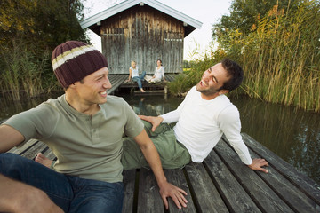 Friends relaxing outside a cottage near the lake.