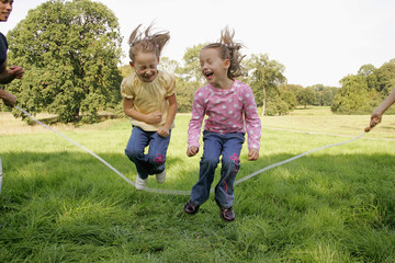 Two sisters jumping over a skipping rope.